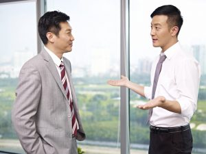 asian businessman standing and talking in office.
