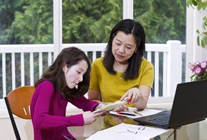 Chinese lady teaching Chinese language to preteen girl at home with green trees in background