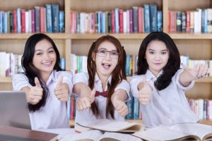 Three beautiful high school students with long hair showing thumbs up on the camera in the library