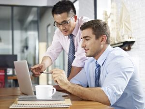 asian and caucasian business executives looking at laptop screen while having a discussion in a multinational company.